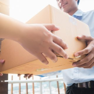 Hand of asia woman are receive a box from delivery man in delivery service concept